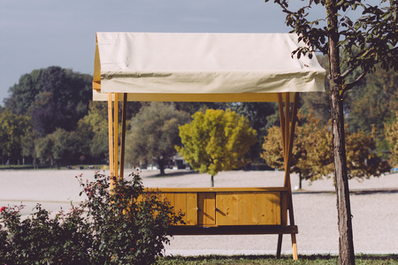 Wooden vendor stand with white awning standing empty in the park