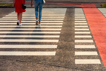 Zebra crossing with red bike lane and two people crossing in the background Stock Photo