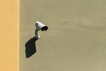 Security camera on a green and yellow house facade Stock Photo