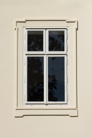 Closed white window on off white building facade