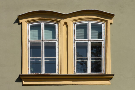 Vintage looking double window in European style, green facade with yellow border Stock Photo
