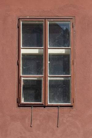Old window, closed on an old brown building facade