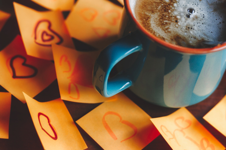 Coffee mug with hot coffee on the table surrounded with post it love notes Stock Photo