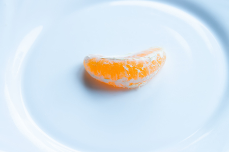 Tangerine wedge peeled on a white plate 스톡 콘텐츠 - 115696195