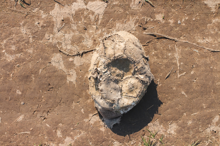 Old worn deflated football ball abandoned in the dirt Stock Photo