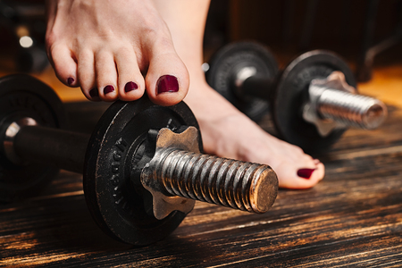 Woman barefoot standing with one feet on a dumbbell, surrounded with workout equipment Stock Photo