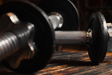 Couple of iron dumbbells one on top of the other lying on a wooden floor