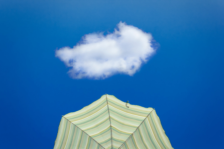 Yellow striped parasol against bright blue sky with one lonely white cloud
