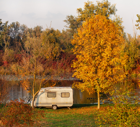 Old vintage looking RV parked by the water surrounded by trees and autumn foliage