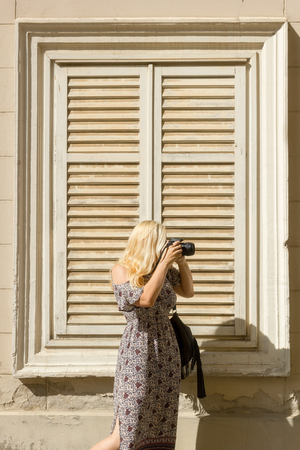Blonde woman in summer dress taking pictures with her camera, standing in front window frame with closed blinds