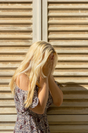 Blonde woman covering her face with hands and crying in front beige window blinds, wearing summer dress