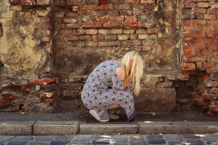 Blond woman in summer dress crouching in front of an old brick wall, hiding her face and crying Stock Photo