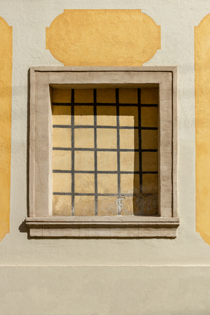 Metal grid covering walled window on an old building exterior Stock Photo
