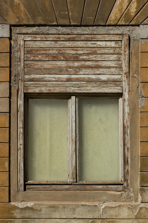 Old wooden window with wooden blinds on an abandoned wooden house Stock Photo