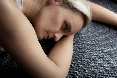 Blond woman, lying on her hands, looking sad, lonely and bored