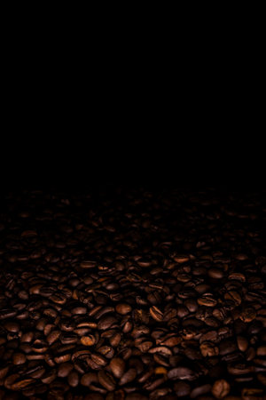Heap of coffee beans in a dark, with black copy space above Stock Photo