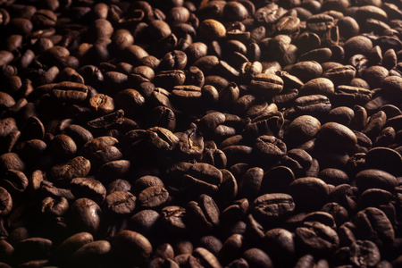 Full frame shot of coffee beans with some light coming from right upper corner