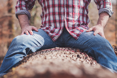 Strong man in plaid shirt and blue jeans sitting on a cut tree trunk, legs spread