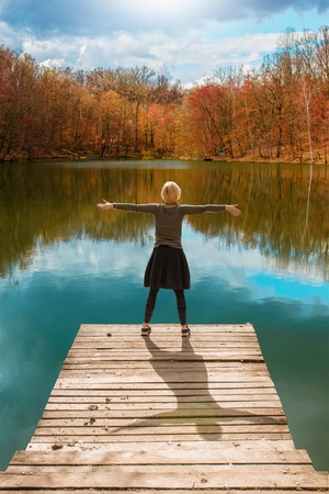 Woman standing on the edge of wooden dock, with her arms raised up, looking at water and colorful autumnal forest