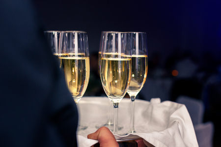 Waiter carrying champagne glasses filled with champagne on a tray in a banquet hall Stock Photo
