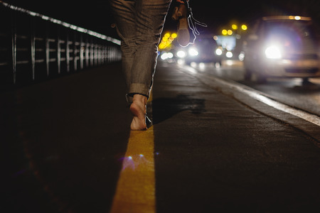 Woman walking bare foot on tip toes in night with incoming traffic, wearing her shoes in her hand