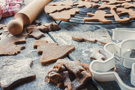 Gingerbread dough, rolled out with different Christmas shapes cut into it and sprinkled with powdered sugar on a table with cookie cutter and rolling pin Stock Photo