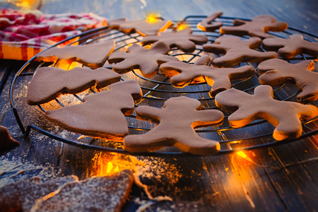 Gingerbread Christmas cookies, shaped as gingerbread man and trees, arranged on a metal tray on the kitchen table with some warm fairy lights underneath