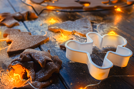 Gingerbread Christmas cookies in shape of trees, sprinkled with powdered sugar on a wooden table with warm orange glow from Christmas lights Stock Photo