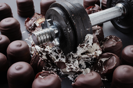 Iron dumbbell dropped in the middle of chocolate covered marshmallows destroying them, diet concept