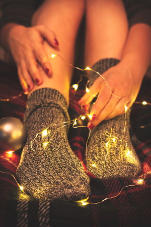 Womans legs in cozy wool socks on a warm red blanket intertwined with fairy lights
