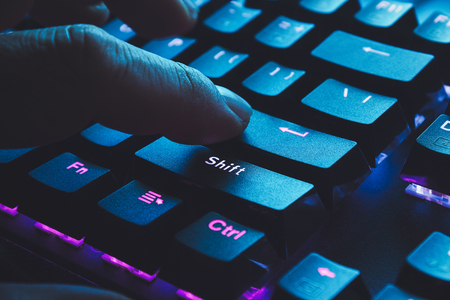 Male hand typing on the black illuminated  keyboard with blue light coming from screen Stock Photo