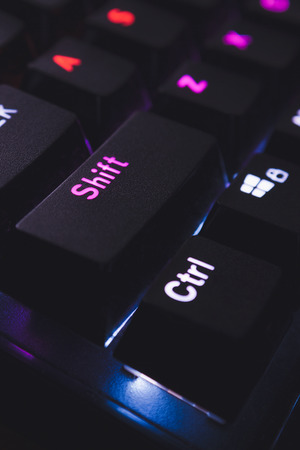 Black keyboard keys with colorful lights underneath, close up