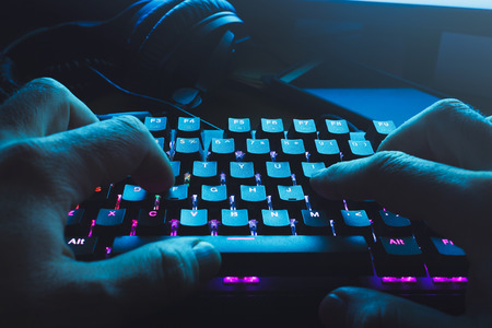 Male hands typing on the black illuminated  keyboard with blue light coming from screen