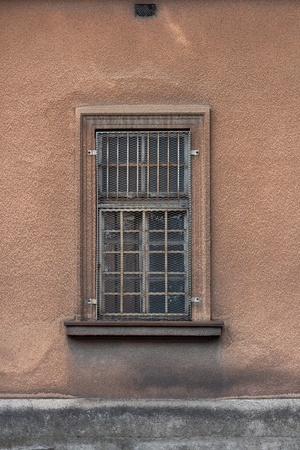 Old brown building with old closed window and metal security bars