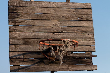Old and rusty basketball hoop with tangled net, on an old wooden backboard