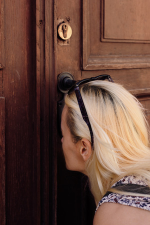 Beautiful blonde woman looking thru keyhole on an old wooden door Stock Photo