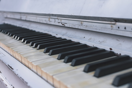 Row of piano keys on an old white piano