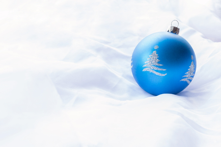 One blue bauble on bright white background