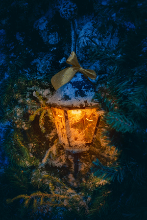 Lantern with orange light glowing inside, hanging from the fir tree in the snowy winter night