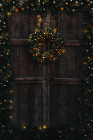 Old wooden door decorated with Christmas garland and wreath, and with warm glowing fairy lights