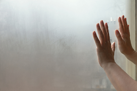 Mysterious female hands in front of blurred window glass