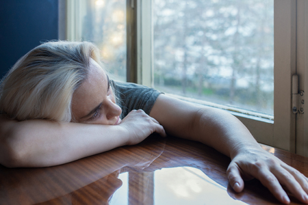 Depressed blonde woman laying on her hands on a kitchen table looking longingly through the window