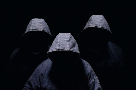 Three mysterious men silhouette with darkened face, no visible face, in blue hoodies on dark background Stock Photo