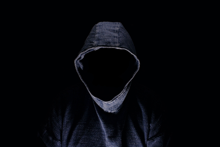 Mysterious man silhouette with darkened face, no visible face, in blue hoodie on dark background Banco de Imagens