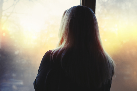 Blonde woman looking out the window into the morning light, back to the camera Stock Photo