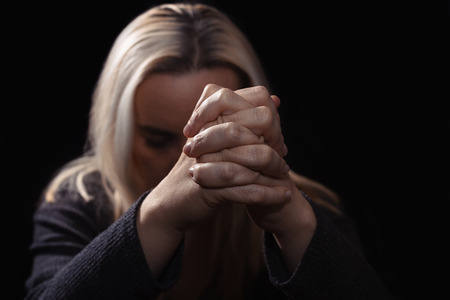 Woman praying with her hands clasped in front of her face, in dark room