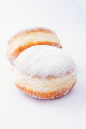 Two freshly made doughnuts filled with jam and covered in powdered sugar on a white background