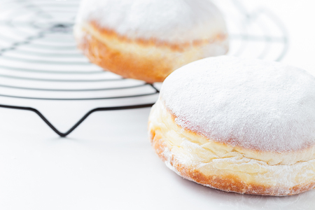 Freshly made doughnuts filled with jam and covered in powdered sugar on a white background on a round baking rack