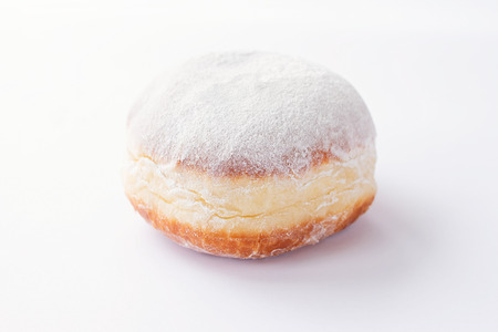 One freshly made doughnuts filled with jam and covered in powdered sugar on a white background