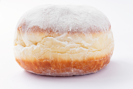 One freshly made doughnut filled with jam and covered in powdered sugar on a white background Stock Photo